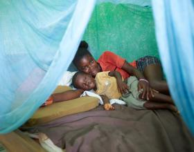 Source - 2016 Sarah Hoibak/VectorWorks, Courtesy of Photoshare. Description - In Ghana, mother and son, Mercy and Daniel, lie under the insecticide treated net (ITN) they received to protect them from malaria.